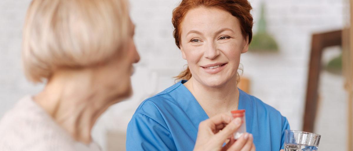 A nurse gives a patient medication. Shutterstock image via user Dmytro Zinkevych
