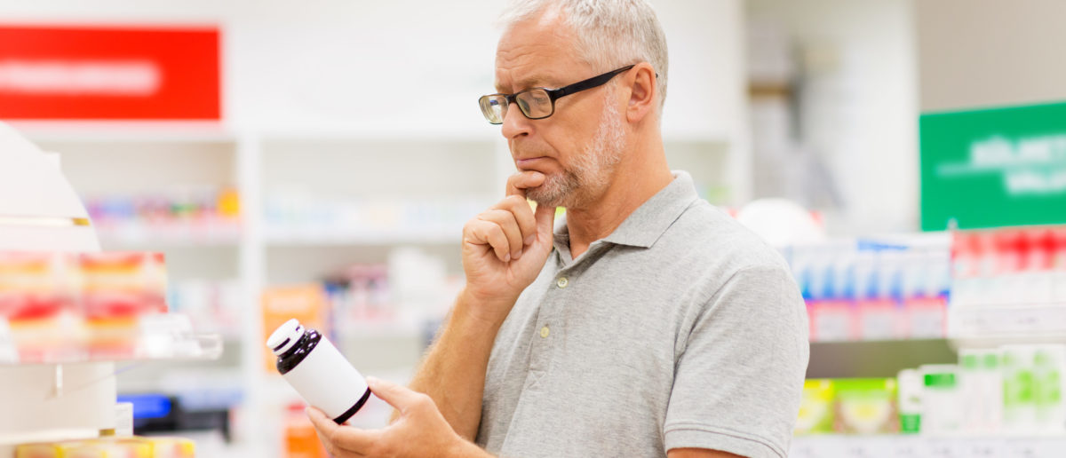 A man examines a bottle of medicine. Shutterstock image via user Syda Productions