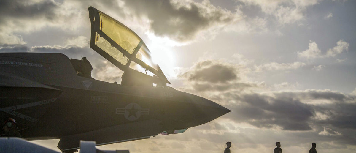 A Marine Corps F-35B Lightning II sits on the flight deck of the Wasp-class amphibious assault ship USS Essex (LHD 2) while Marines with Marine Fighter Attack Squadron 211, 13th Marine Expeditionary Unit (MEU), prepare for flight operations. (U.S. Marine Corps photo by Cpl. Francisco J. Diaz Jr./Released)