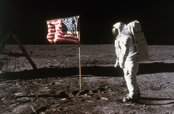Astronaut Buzz Aldrin, lunar module pilot, stands beside an American flag placed on the moon during Apollo 11 extravehicular activity. He is photographed by the mission's commander, Neil A. Armstrong, 1969. Location Moon.