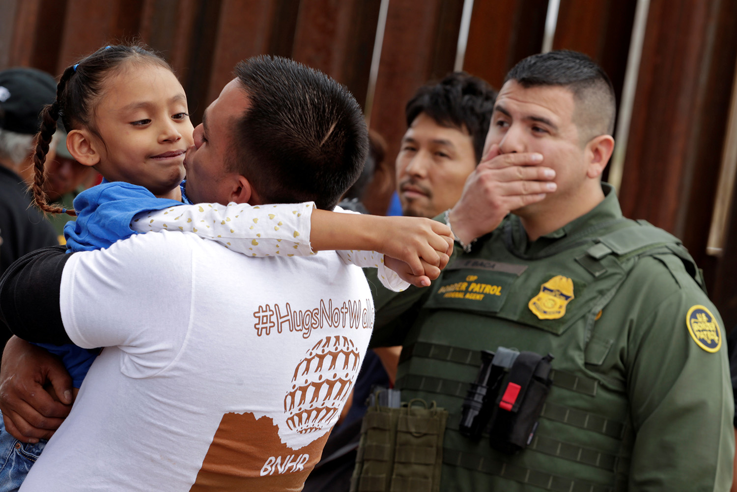 "A man embraces a child as an U.S. border patrol federal agent reacts during a brief reunification meeting of relatives separated by deportation and immigration called ""Hugs, No Walls"", at the border fence between Mexico and U.S in Ciudad Juarez, Mexico October 13, 2018. REUTERS/Jose Luis Gonzalez"