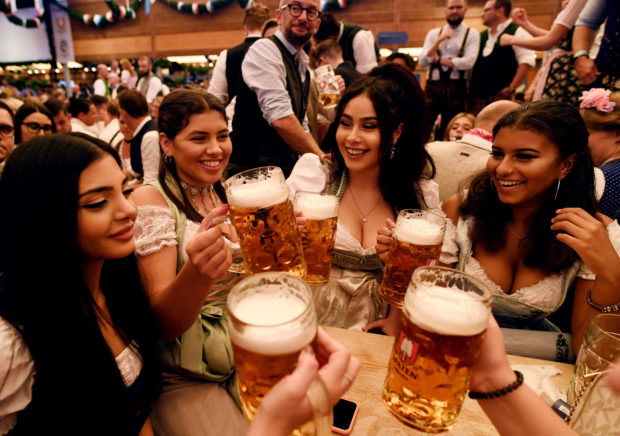 Visitors cheer with beers during the opening day of the 185th Oktoberfest in Munich