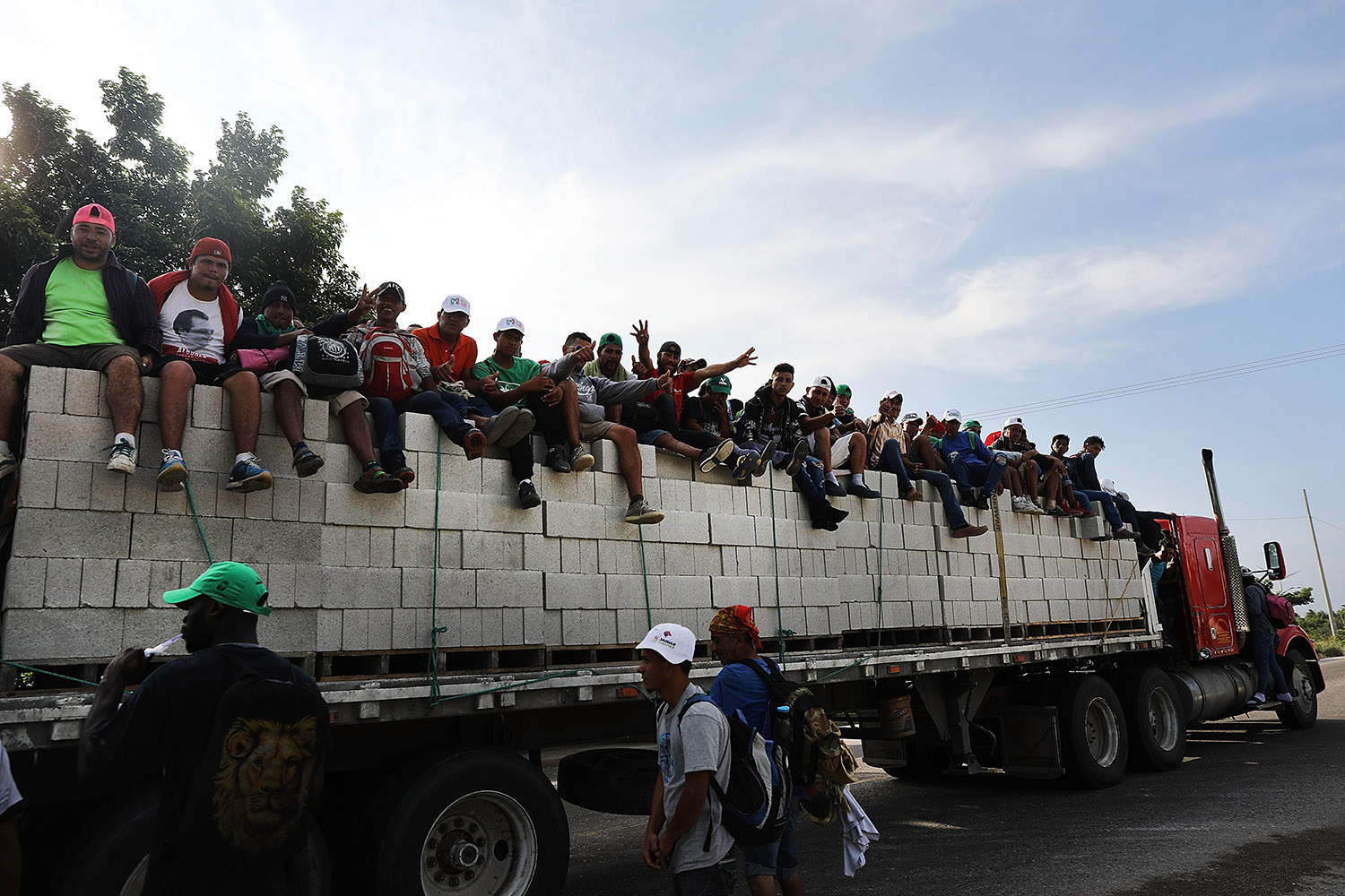 Some of the thousands of Central American migrants in the caravan get a lift to a camp for the evening on October 30, 2018 in Juchitan de Zaragoza, Mexico. Following a break on Sunday, the migrants, many of them fleeing violence in their home countries, resumed their march towards the United States border. As fatigue from the heat, distance and poor sanitary conditions has set in, the numbers of people participating in the march has slowly dwindled but a significant group are determined to get to the United Sates. It has been widely reported that the Pentagon will deploy up to 5,200 active-duty troops to the U.S.-Mexico border in an effort to prevent members of the migrant caravan from illegally entering the country. (Photo by Spencer Platt/Getty Images)