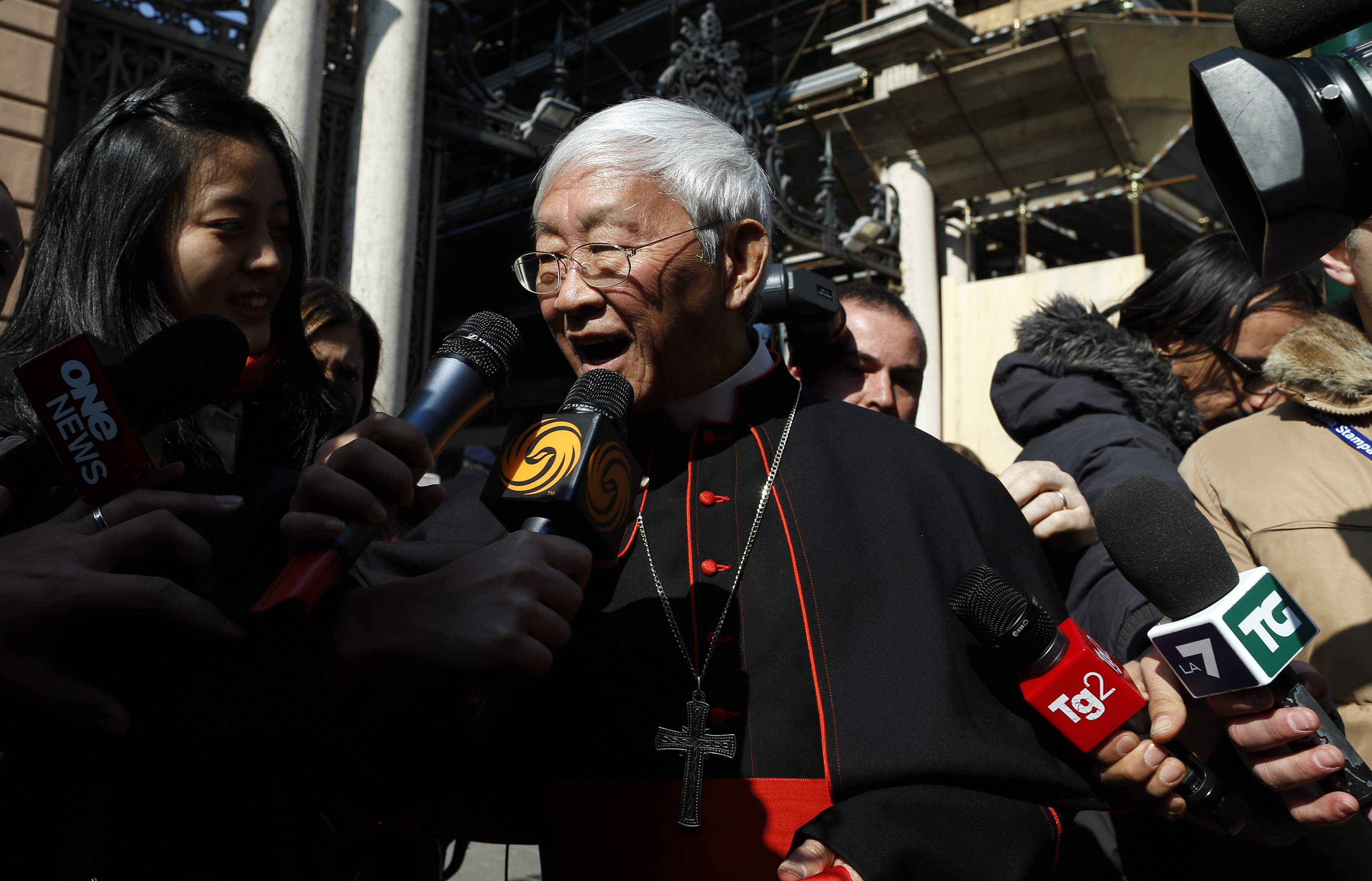 Cardinal Joseph Zen Ze-kiun of China is surrounded by media as he walks near St. Peter square in Rome February 28, 2013. Pope Benedict left the Vatican on Thursday after pledging unconditional obedience to whoever succeeds him to guide the Roman Catholic Church at one of the most crisis-ridden periods in its 2,000-year history. REUTERS/Alessandro Bianchi