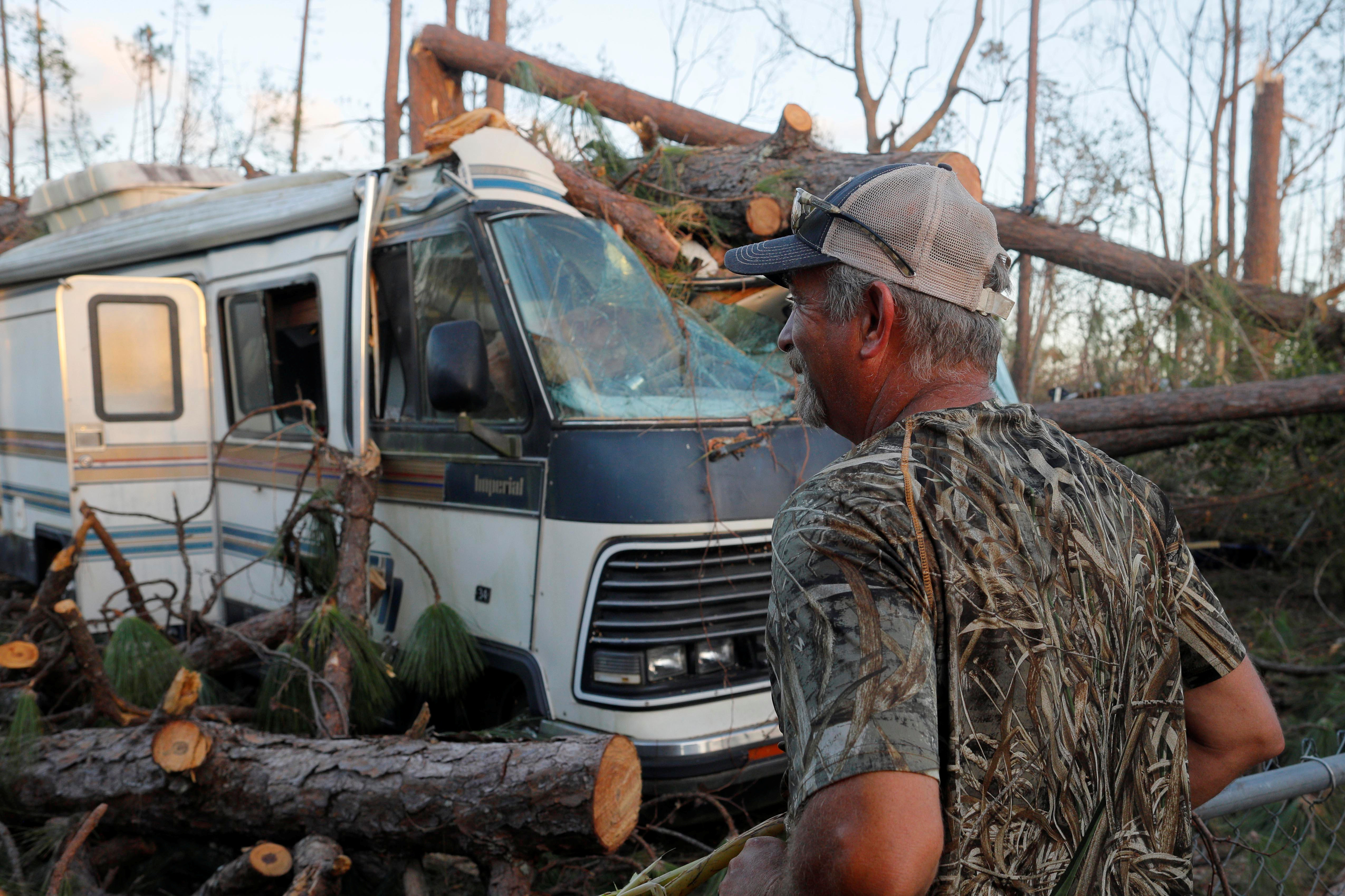 Chuck Pester looks over the damage to his RV and back yard caused by Hurricane Michael in St. Andrews Bay