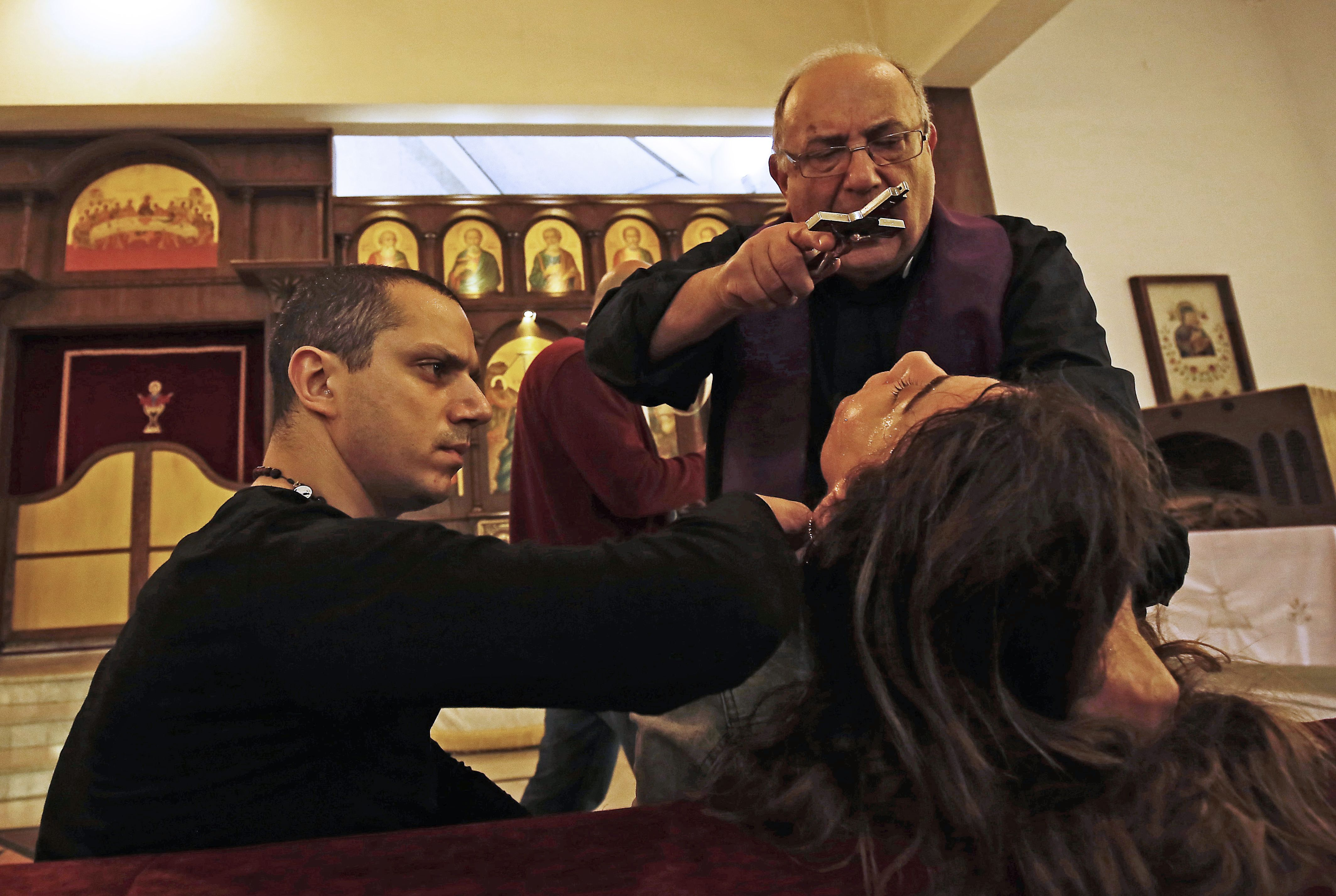 Father Elias Rahal, 68, performs exorcism ritual on a Lebanese lady at a church in the district of Mina in the northern port city of Tripoli on April 19, 2018. (IBRAHIM CHALHOUB/AFP/Getty Images)
