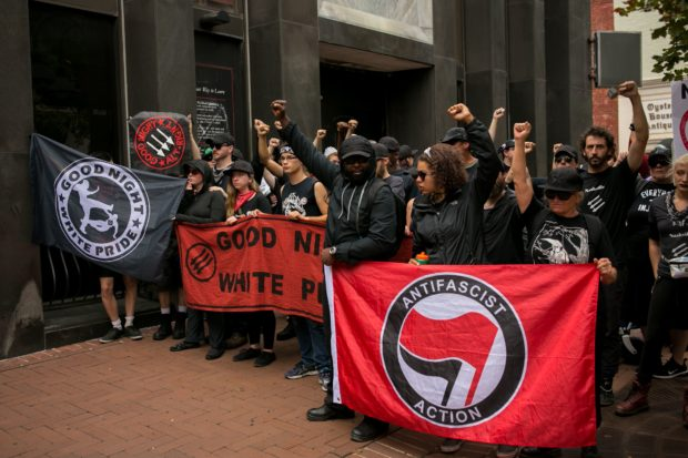 Members of ANTIFA get in formation after entering the security checkpoint required to enter the mall in downtown Charlottesville, Virginia, one-year after the violent white nationalist rally that left one person dead and dozens injured. (Photo by Logan Cyrus / AFP) (Photo credit should read LOGAN CYRUS/AFP/Getty Images)