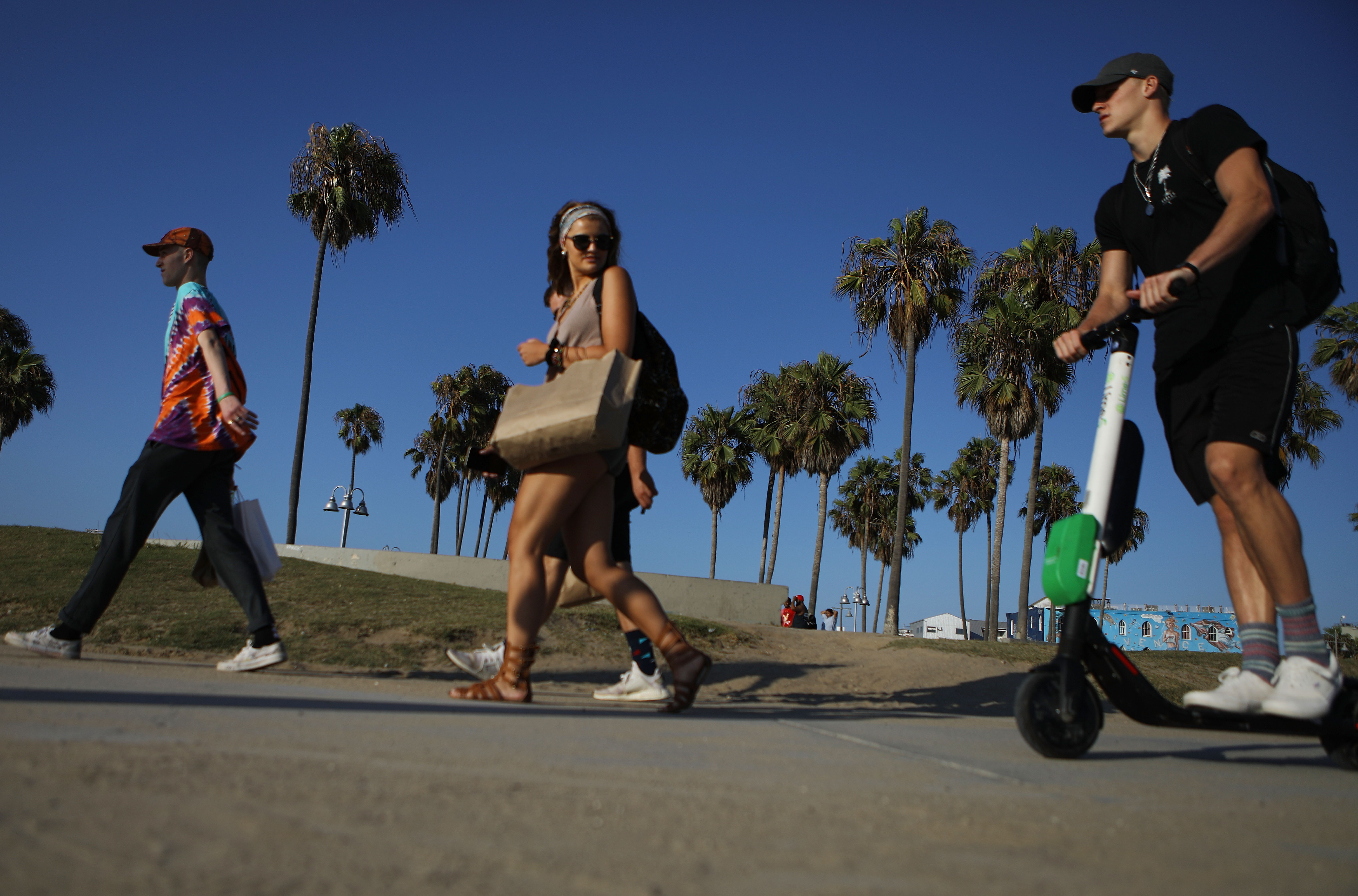 A man rides a Lime shared dockless electric scooter along Venice Beach on August 13, 2018 in Los Angeles, California. Mario Tama/Getty Images