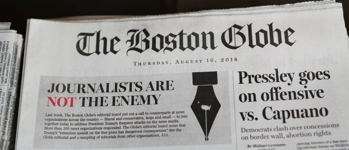"""CAMBRIDGE, MA - AUGUST 16: The front page of the Thursday, August 16, 2018 edition of the Boston Globe newspaper reads """"Journalists are Not the Enemy"""" as it sits for sale at Out of Town News on August 16, 2018 in Cambridge, Massachusetts. Hundreds of U.S. newspapers joined together and published editorials decrying President Donald Trump's description of the media as the """"enemy of the people."""" (Photo by Tim Bradbury/Getty Images)"""