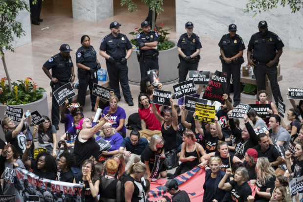 WASHINGTON, DC - OCTOBER 4: Protestors rally against Supreme Court nominee Judge Brett Kavanaugh in the atrium of the Hart Senate Office Building on Capitol Hill, October 4, 2018 in Washington, DC. Kavanaugh's confirmation process was halted for less than a week so that FBI investigators could look into allegations by Dr. Christine Blasey Ford, a California professor who has accused Kavanaugh of sexually assaulting her during a party in 1982 when they were high school students in suburban Maryland. (Photo by Drew Angerer/Getty Images)