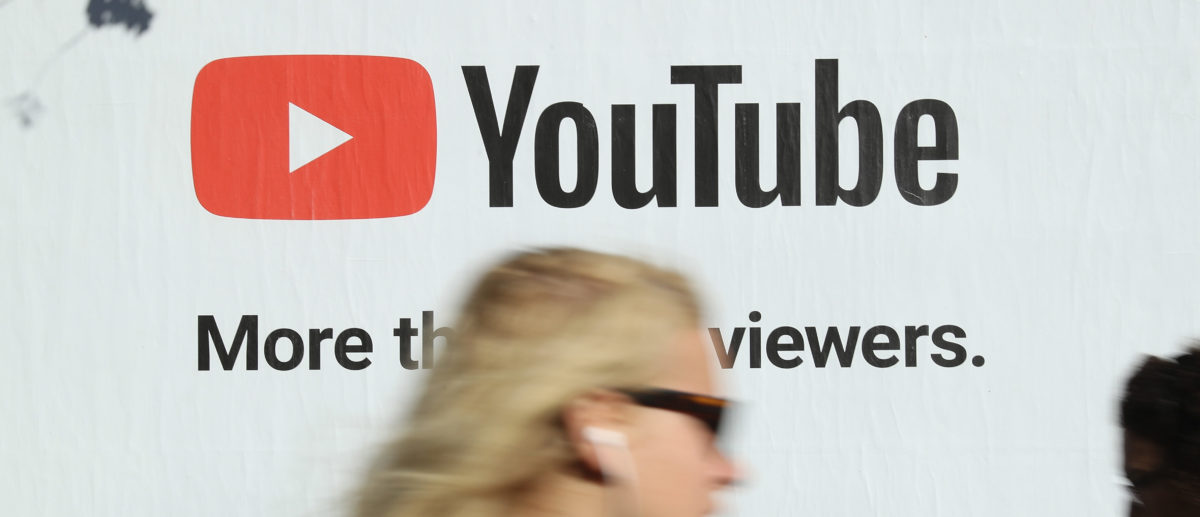 A young woman walks past a billboard advertisement for YouTube on October 5, 2018 in Berlin, Germany. Sean Gallup/Getty Images