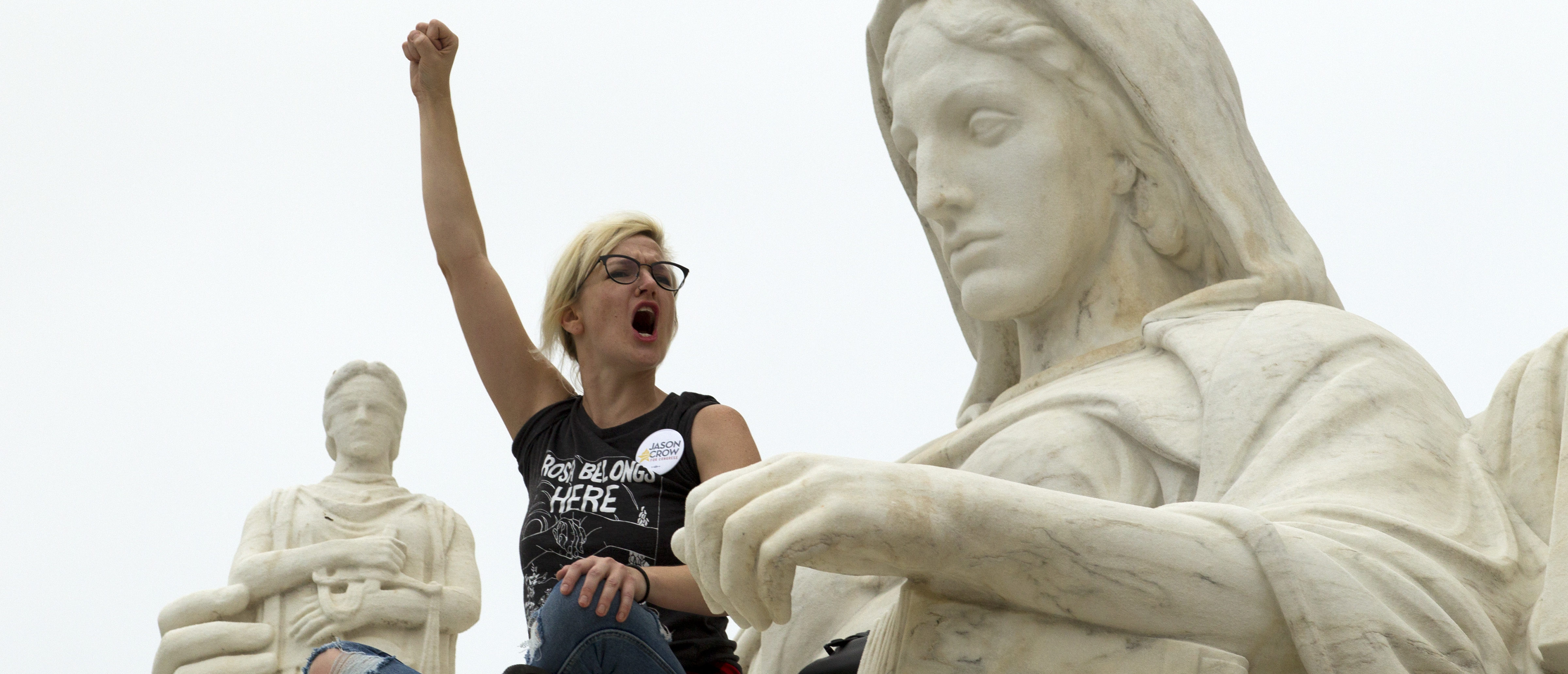 """TOPSHOT - Demonstrator Jessica Campbell-Swanson of Denver, stands on the lap of the """"Contemplation of Justice"""" statue as protestors take the steps of the US Supreme Court protesting against the appointment of Supreme Court nominee Brett Kavanaugh at Capitol Hill in Washington DC, on October 6, 2018. (Photo by Jose Luis Magana / AFP) (Photo credit should read JOSE LUIS MAGANA/AFP/Getty Images)"""