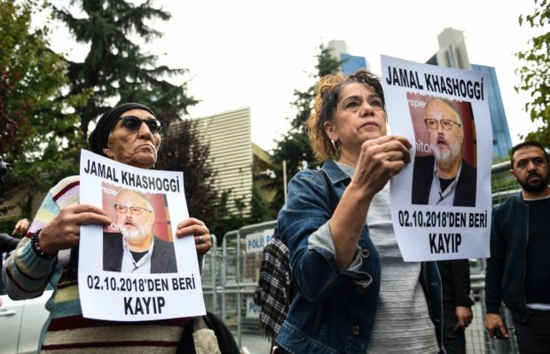"""Members of Human Rights Association (IHD) hold portraits of missing journalist Jamal Khashoggi reading """"Jamal Khashoggi is missing since October 2"""" during a demonstration outside Saudi Arabia's consulate in Istanbul on October 9, 2018. KILIC/AFP/Getty Images"""