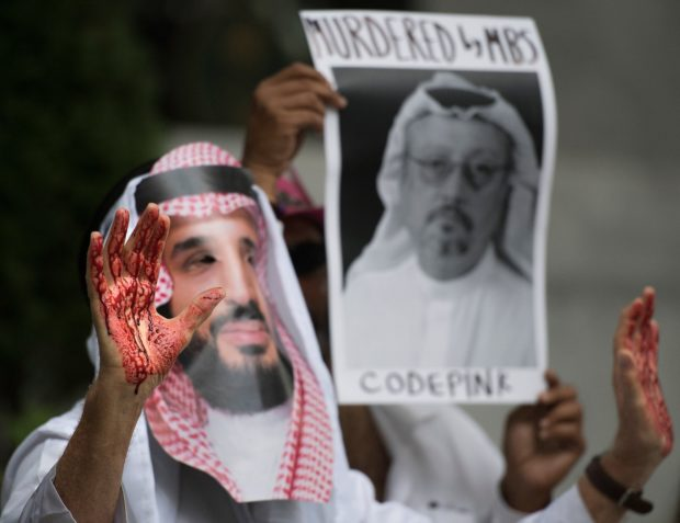 """A demonstrator dressed as Saudi Arabian Crown Prince Mohammed bin Salman (C) with blood on his hands protests outside the Saudi Embassy in Washington, DC, on October 8, 2018, demanding justice for missing Saudi journalist Jamal Khashoggi. - US President Donald Trump said October 10, 2018 he has talked to Saudi authorities """"at the highest level"""" to demand answers over what happened to missing journalist Jamal Khashoggi. Trump told reporters at the White House that he talked to the Saudi leadership """"more than once"""" since Khashoggi, a US resident and Washington Post contributor, vanished on October 2 after entering the Saudi consulate in Istanbul. (Photo by Jim WATSON / AFP) (Photo credit should read JIM WATSON/AFP/Getty Images)"""