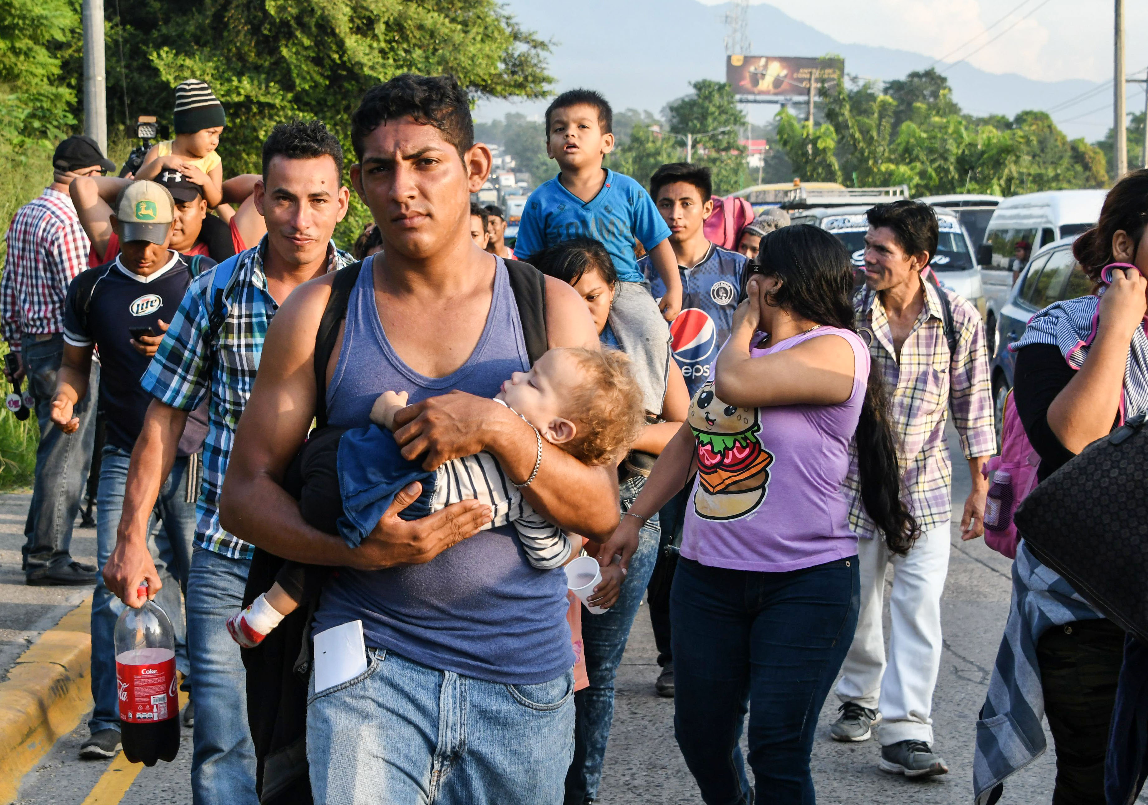 An Honduran man carries a child on is arms during an exodus towards the US from San Pedro Sula, 180 kms north from Tegucigalpa, on October 13, 2018. (Photo: ORLANDO SIERRA/AFP/Getty Images)