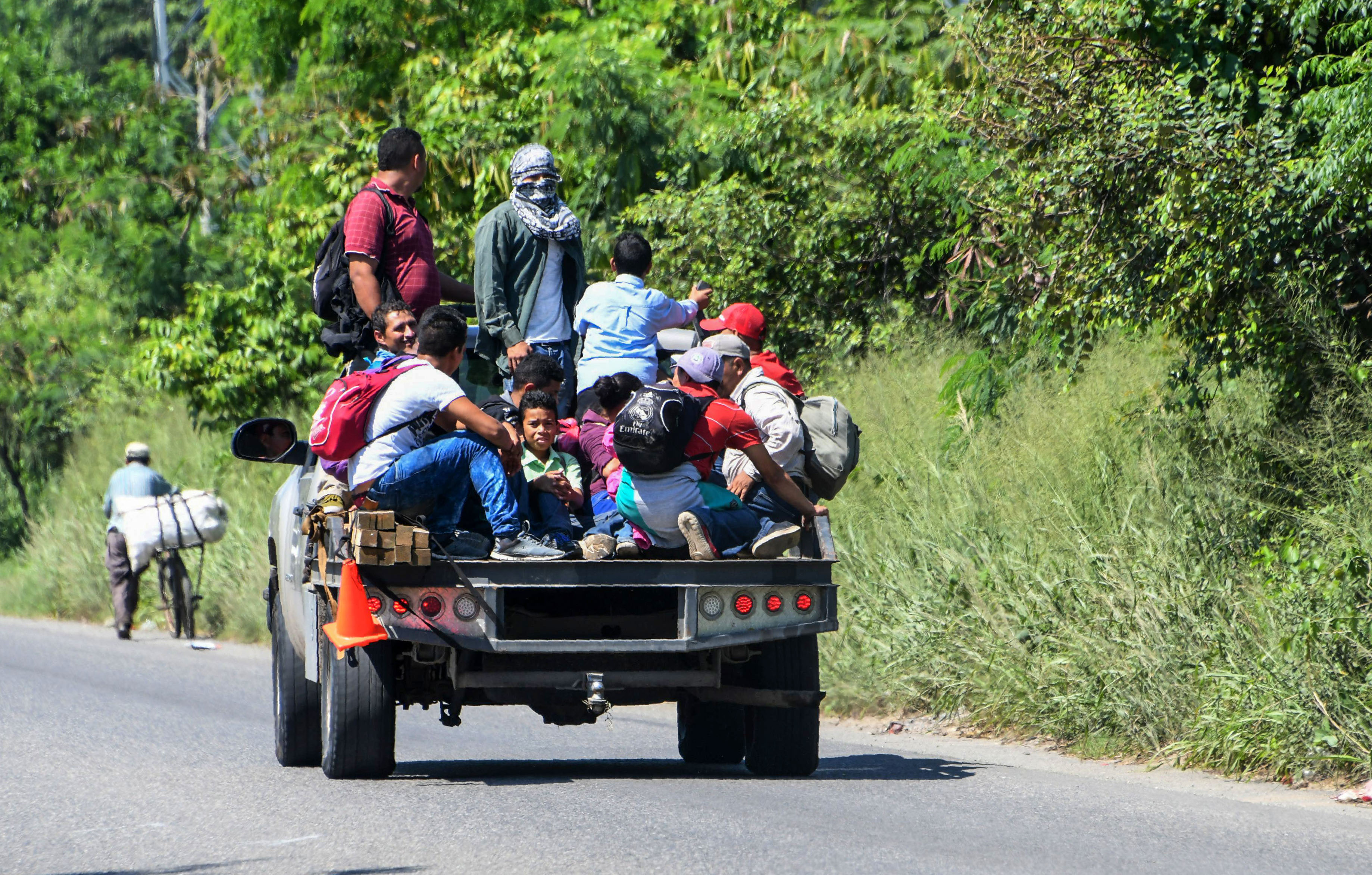 Hondurans get on vans and trucks during the exodus towards the US from San Pedro Sula, 180 kms north from Tegucigalpa, on October 13, 2018. (Photo: ORLANDO SIERRA/AFP/Getty Images)