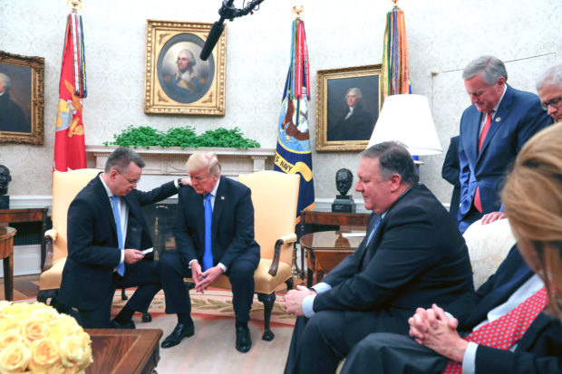 US pastor Andrew Brunson prays for US President Donald Trump as they meet in the Oval Office of the White House in Washington, DC, October 13, 2018. - Brunson, held for two years in Turkey, returned to the US earlier Saturday after a court freed him in a case that sparked a crisis in Ankara's ties with Washington and trouble for its economy. The court in the western town of Aliaga convicted Brunson on terror-related charges and sentenced him to three years, one month and 15 days in jail. (Photo by ROBERTO SCHMIDT / AFP) (Photo credit should read ROBERTO SCHMIDT/AFP/Getty Images)