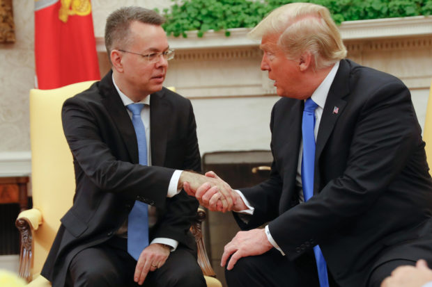 Freed American pastor Andrew Brunson (L) shakes hands with US President Donald Trump at the White House in Washington, DC, October 13, 2018. - Brunson, held for two years in Turkey, returned to the US earlier Saturday after a court freed him in a case that sparked a crisis in Ankara's ties with Washington and trouble for its economy. The court in the western town of Aliaga convicted Brunson on terror-related charges and sentenced him to three years, one month and 15 days in jail. (Photo by ROBERTO SCHMIDT / AFP) (Photo credit should read ROBERTO SCHMIDT/AFP/Getty Images)