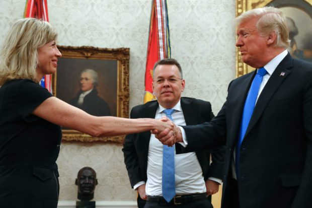 Freed American pastor Andrew Brunson (C) looks on as his wife Norine shakes hands with US President Donald Trump after a meeting in the Oval Office at the White House in Washington, DC, October 13, 2018. - Brunson, held for two years in Turkey, returned to the US earlier Saturday after a court freed him in a case that sparked a crisis in Ankara's ties with Washington and trouble for its economy. The court in the western town of Aliaga convicted Brunson on terror-related charges and sentenced him to three years, one month and 15 days in jail. (Photo by ROBERTO SCHMIDT / AFP) (Photo credit should read ROBERTO SCHMIDT/AFP/Getty Images)