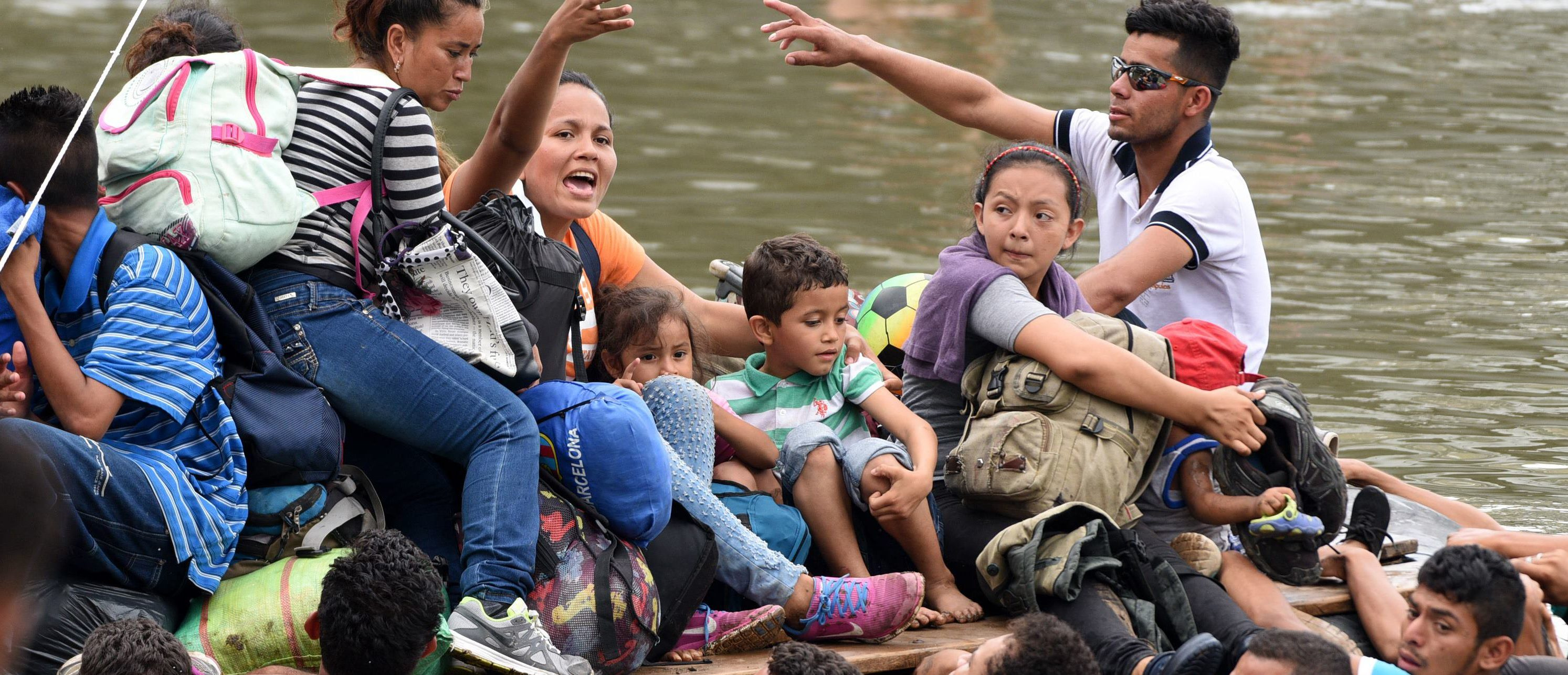 Honduran migrants taking part in a caravan to the US, cross the Suchiate River, natural border between Guatemala and Mexico, in Ciudad Tecun Uman, Guatemala, on October 20, 2018. - Thousands of migrants who forced their way through Guatemala's northwestern border and flooded onto a bridge leading to Mexico, where riot police battled them back, on Saturday waited at the border in the hope of continuing their journey to the United States. (Photo by ORLANDO SIERRA / AFP)