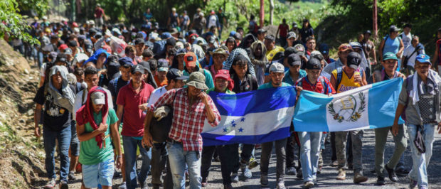 Honduran migrants take part in a new caravan heading to the US with Honduran and Guatemalan national flags in Quezaltepeque, Chiquimula, Guatemala on Oct/ 22, 2018. -- U.S. President Donald Trump on Monday called the migrant caravan heading toward the US-Mexico border a national emergency, saying he has alerted the U.S. border patrol and military. (Photo by ORLANDO ESTRADA / AFP)
