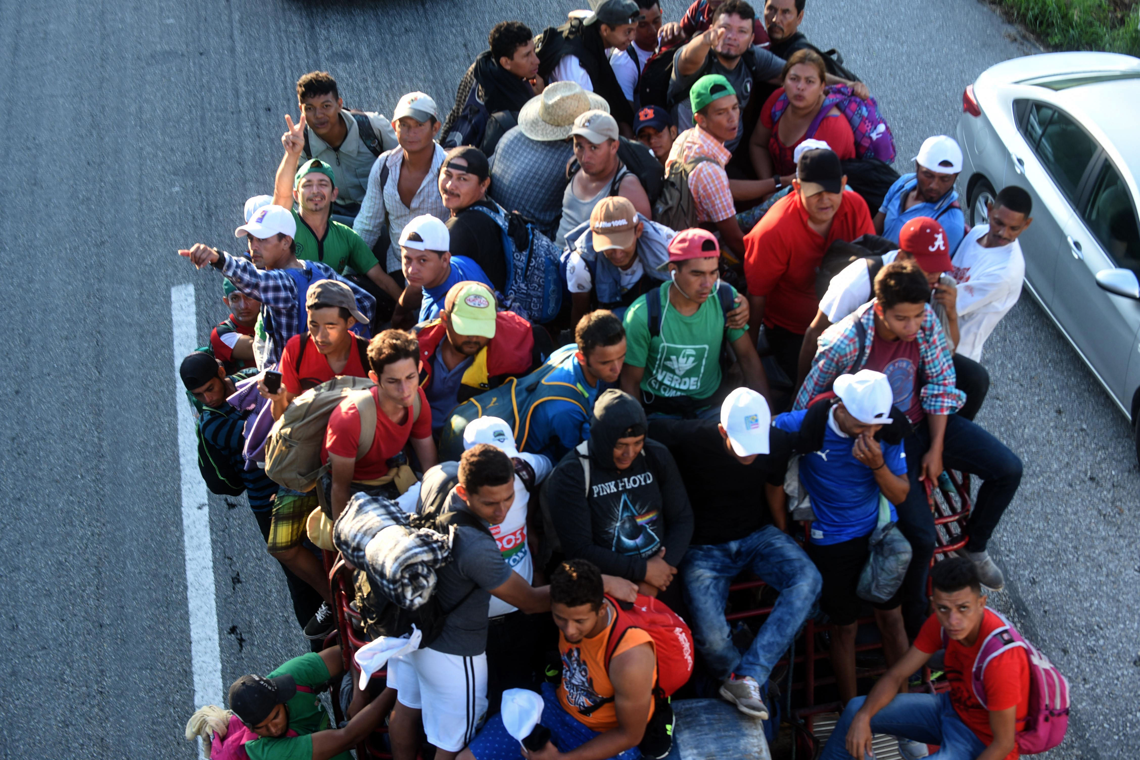 TOPSHOT - Honduran migrants heading in a caravan to the US, travel aboard a truck in Mapastepec on their way to Pijijiapan Chiapas state, Mexico, on October 25, 2018. - Thousands of Central American migrants crossing Mexico toward the United States in a caravan have resumed their long trek, walking about 12 hours to their next destination. (Photo by Johan ORDONEZ / AFP)