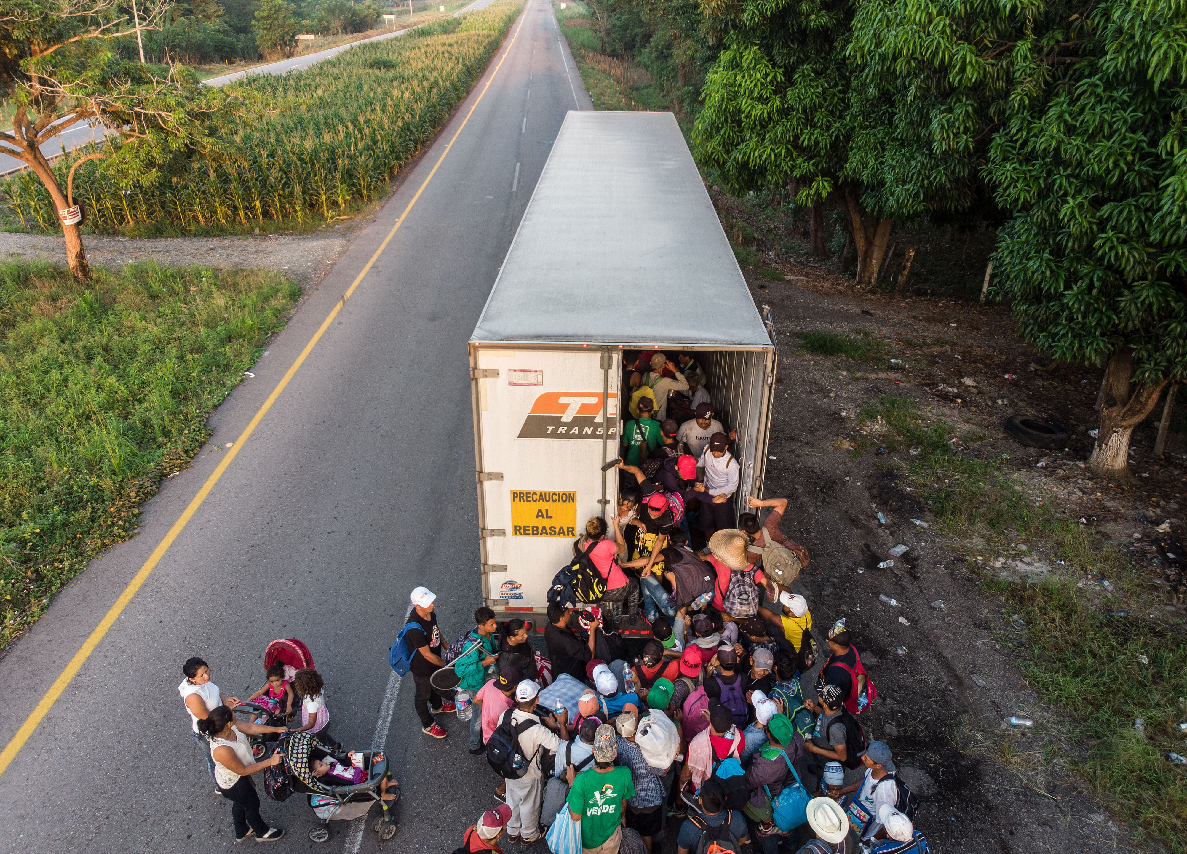 "Honduran migrants taking part in a caravan heading to the US, get on a truck, near Pijijiapan, southern Mexico on October 26, 2018. - The Pentagon is expected to deploy about 800 troops to the US-Mexico border, two US officials told AFP on Thursday, after President Donald Trump said the military would help tackle a ""national emergency"" and called on a caravan of US-bound migrants to turn around. (Photo by Guillermo Arias / AFP)"
