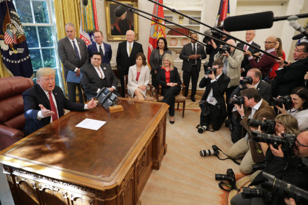 "WASHINGTON, DC - OCTOBER 17: U.S. President Donald Trump (L) talks to reporters while hosting workers and members of his cabinet for a meeting in the Oval Office at the White House October 17, 2018 in Washington, DC. The White House said the meeting was on ""Cutting the Red Tape, Unleashing Economic Freedom."" (Photo by Chip Somodevilla/Getty Images)"