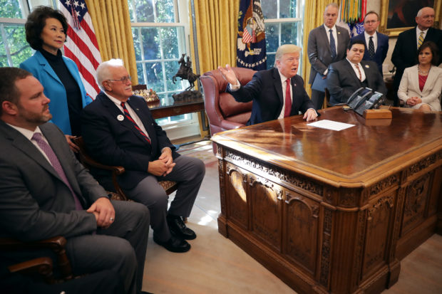 "WASHINGTON, DC - OCTOBER 17: U.S. President Donald Trump (C) talks to journalists while hosting workers and members of his cabinet for a meeting in the Oval Office at the White House October 17, 2018 in Washington, DC. The White House said the meeting was on ""Cutting the Red Tape, Unleashing Economic Freedom."" (Photo by Chip Somodevilla/Getty Images)"
