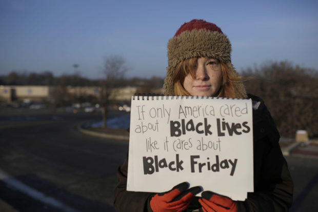 FERGUSON, MO - NOVEMBER 28 : A demonstrator protesting the shooting death of Michael Brown holds a sign near the entrance to a local Walmart store on Black Friday, November 28, 2014 in Ferguson, Missouri. Some local businesses remain closed to consumers in Ferguson as tensions remain high in the community after Michael Brown, an 18-year-old black male teenager, was fatally wounded by Darren Wilson, a white Ferguson Police officer, on August 9, 2014. A St. Louis County 12-member grand jury decided Monday not to indict Wilson with charges, sparking riots throughout Ferguson. (Photo by Joshua Lott/Getty Images)