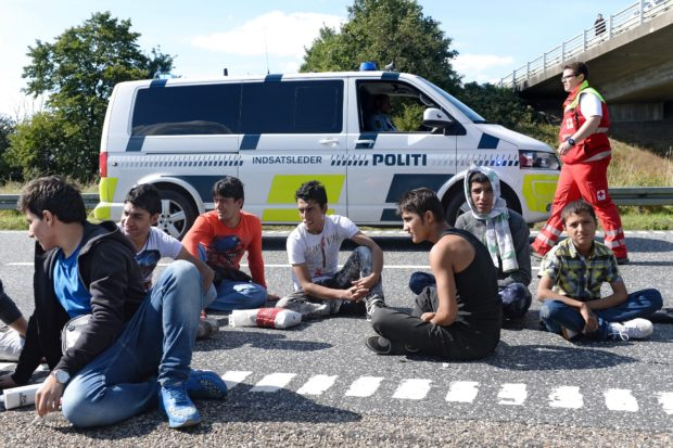 Migrants, mainly from Syria and Iraq, sit in front of a Danish police van, as they attempt to walk at the E45 freeway from Padborg, on the Danish-German border, towards Sweden, on September 9, 2015. The migrants arrived this morning with a train from Germany and were placed at a school from where they fled. AFP PHOTO / SCANPIX DENMARK / Claus Fisker ++++ DENMARK OUT (Photo credit should read CLAUS FISKER/AFP/Getty Images)