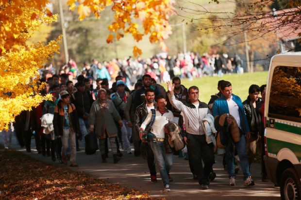 PASSAU, GERMANY - OCTOBER 28: German police lead arriving migrants alongside a street to a transport facility after gathering them at the border to Austria on October 28, 2015 near Wegscheid, Germany. Bavarian Governor Horst Seehofer has accused the Austrian government of wantonly shuttling migrants in buses from the Slovenian border across Austria and dumping them at all hours of day and night at the border to Germany. German authorities have recorded over 7,000 migrants arriving daily since the weekend as a bottleneck of migrants in Slovenia and Croatia finally arrived in Austria. Germany has registered over 800,000 migrants this year and Chancellor Angela Merkel is mounting pressure on European Union member states that so far have shown great reluctance to accept any migrants at all to finally share the burden of accommodating the newcomers, many of whom are refugees fleeing war-torn Syria. (Photo by Johannes Simon/Getty Images)