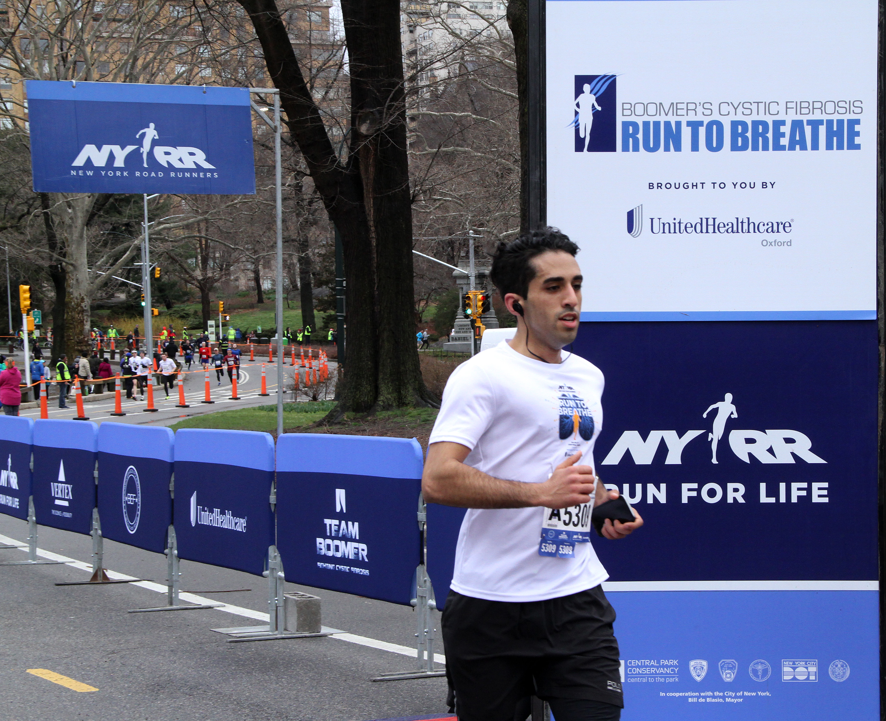 """Race finishers cross the finish line during Boomer's Cystic Fibrosis """"Run To Breathe"""" Charity Event at Central Park Bandshell on April 1, 2017 in New York City. Donna Ward/Getty Images"""