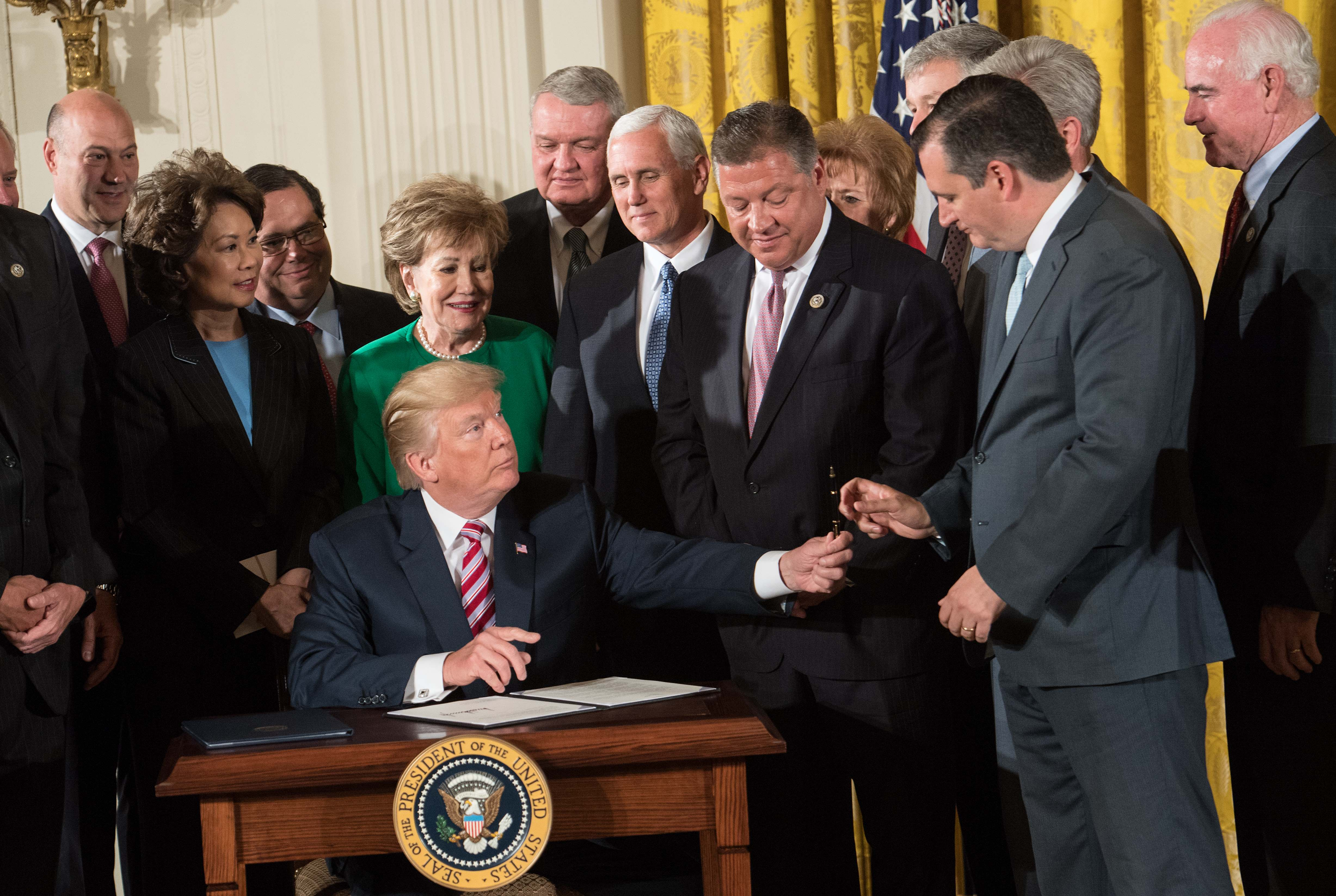 US President Donald Trump hands a pen to Republican US Senator from Texas Ted Cruz after signing a letter of principles on air traffic control reform after announcing the Air Traffic Control Reform Initiative in the East Room at the White House in Washington, DC, on June 5, 2017. (Photo: NICHOLAS KAMM/AFP/Getty Images)
