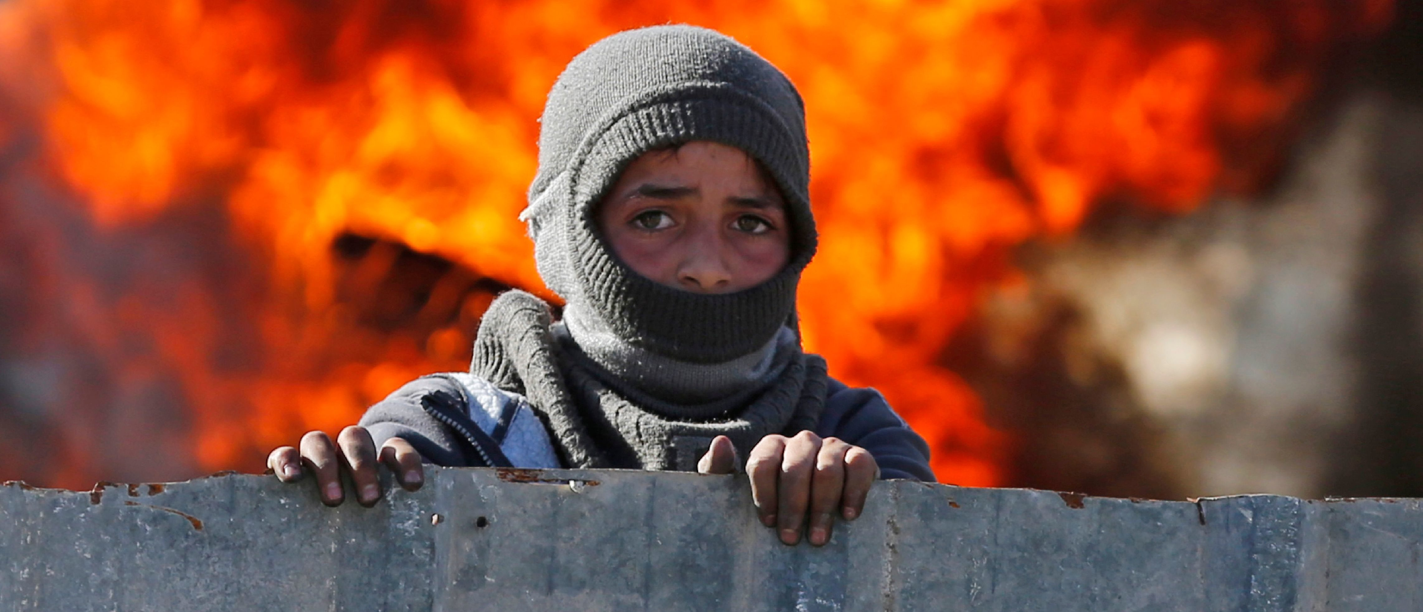 A masked Palestinian boy stands in front of flames during clashes with Israeli soldiers at the entrance of the northern village of Qusra in the occupied West Bank near Nablus on December 4, 2017. An Israeli settler shot dead a Palestinian in the occupied West Bank last week after a group of Israelis was targeted by Palestinian stone-throwers, officials said. / AFP PHOTO / ABBAS MOMANI (Photo credit should read ABBAS MOMANI/AFP/Getty Images)