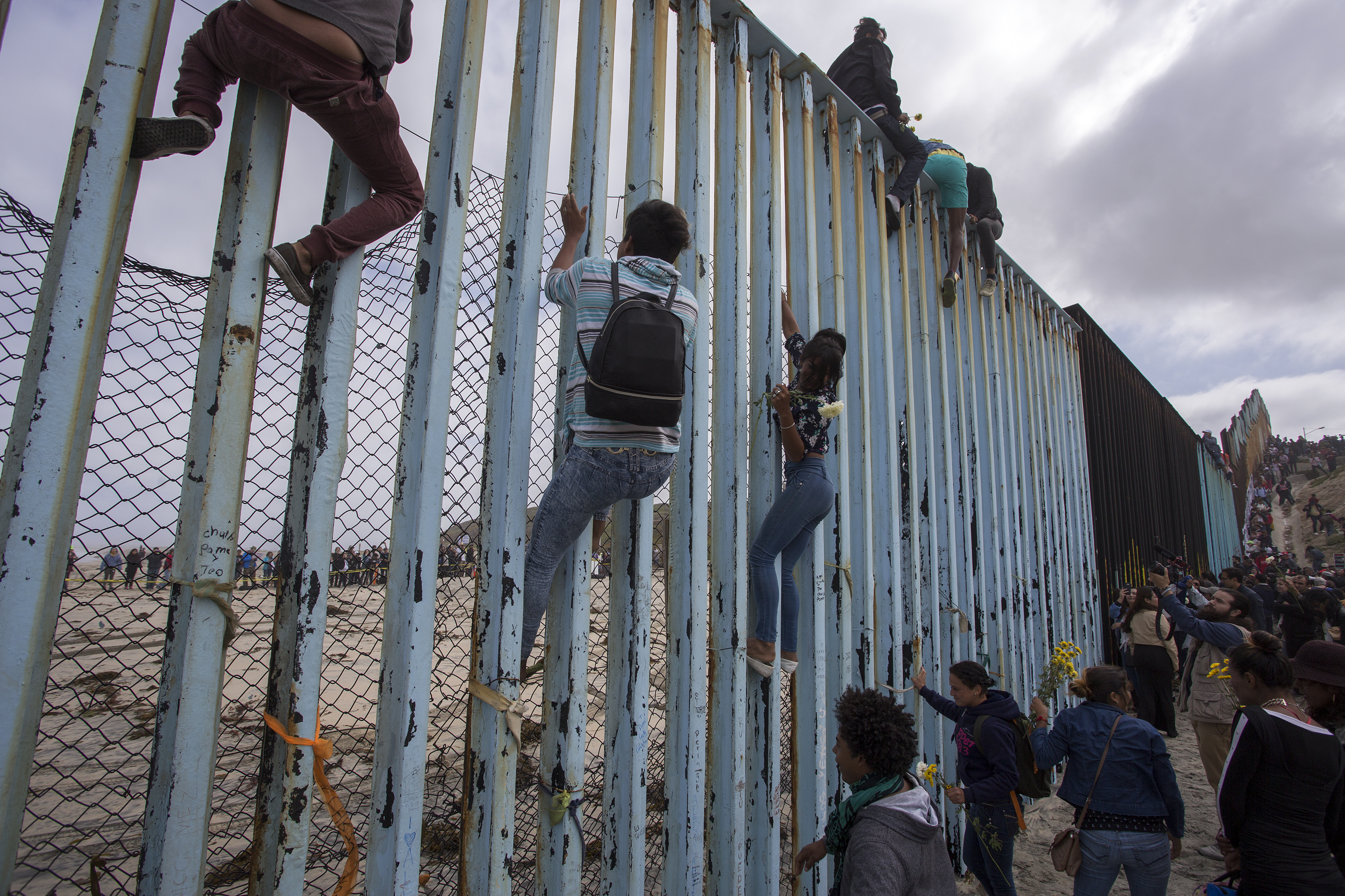TIJUANA, MEXICO - APRIL 29: People climb a section of border fence to look into the U.S. as members of a caravan of Central American asylum seekers arrive to a rally on April 29, 2018 in Tijuana, Baja California Norte, Mexico. More than 300 immigrants, the remnants of a caravan of Central Americans that journeyed across Mexico to ask for asylum in the United States, have reached the border to apply for legal entry. (Photo by David McNew/Getty Images)