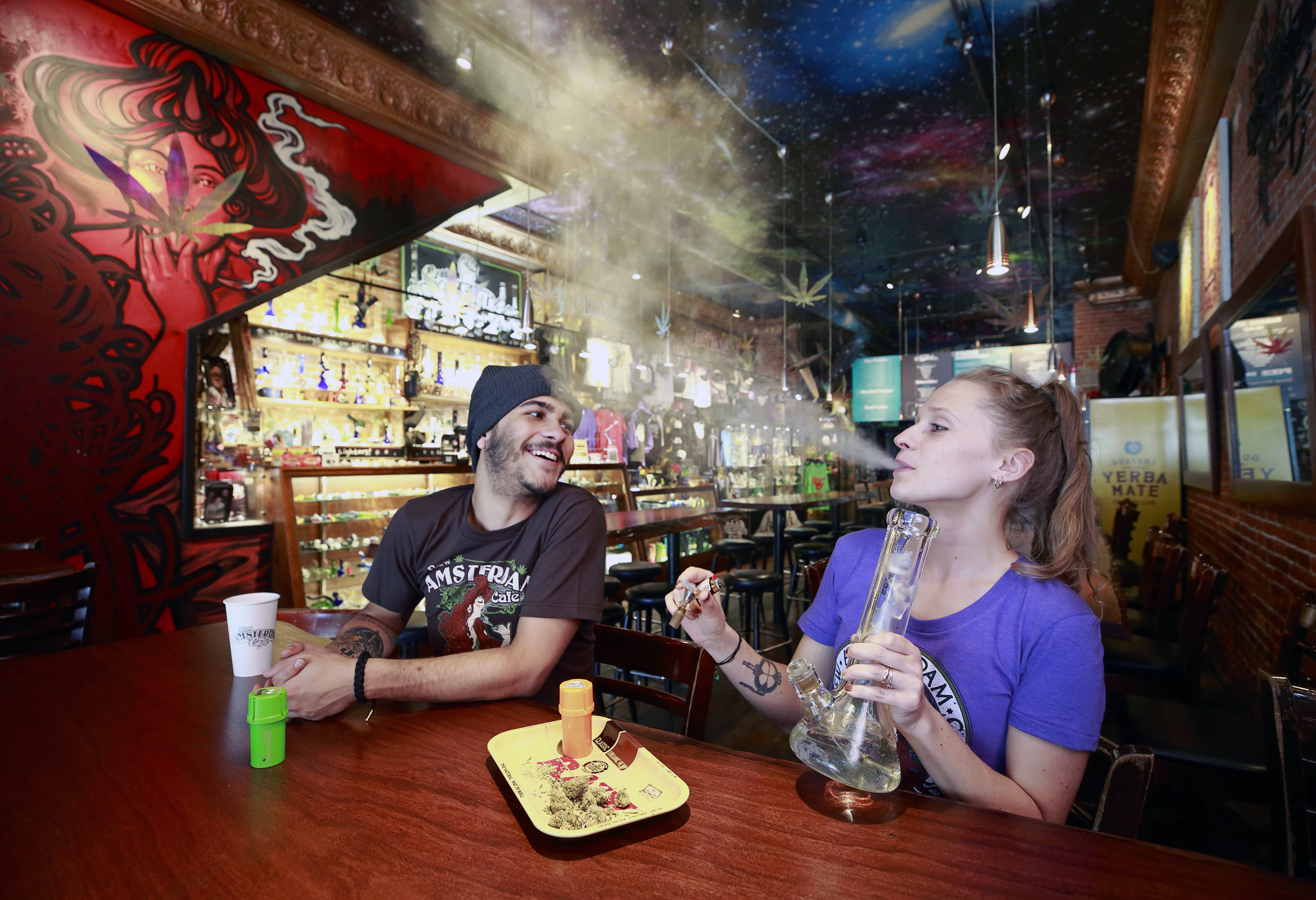Rodrigo Acevedo Casino looks on as Anna Bolechowska smokes marijuana with a bong at the New Amsterdam Cafe June 20, 2018 in Vancouver, British Columbia, Canada. Jeff Vinnick/Getty Images