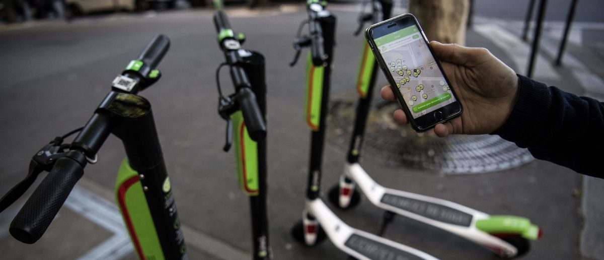 A man shows the mobile application allowing to check the availability of electric scooters of the US company Lime on the day of their launch in Paris on June 22, 2018. (Photo by Christophe ARCHAMBAULT / AFP) (Photo credit should read CHRISTOPHE ARCHAMBAULT/AFP/Getty Images)