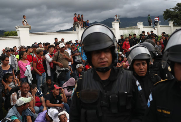 A caravan of more than 1,500 Honduran migrants pauses at a Guatemalan police checkpoint after crossing the border from Honduras on October 15, 2018 in Esquipulas, Guatemala. The caravan, the second of 2018, began Friday in San Pedro Sula, Honduras with plans to march north through Guatemala and Mexico en route to the United States. Honduras has some of the highest crime and poverty rates in Latin America. (Photo by John Moore/Getty Images)