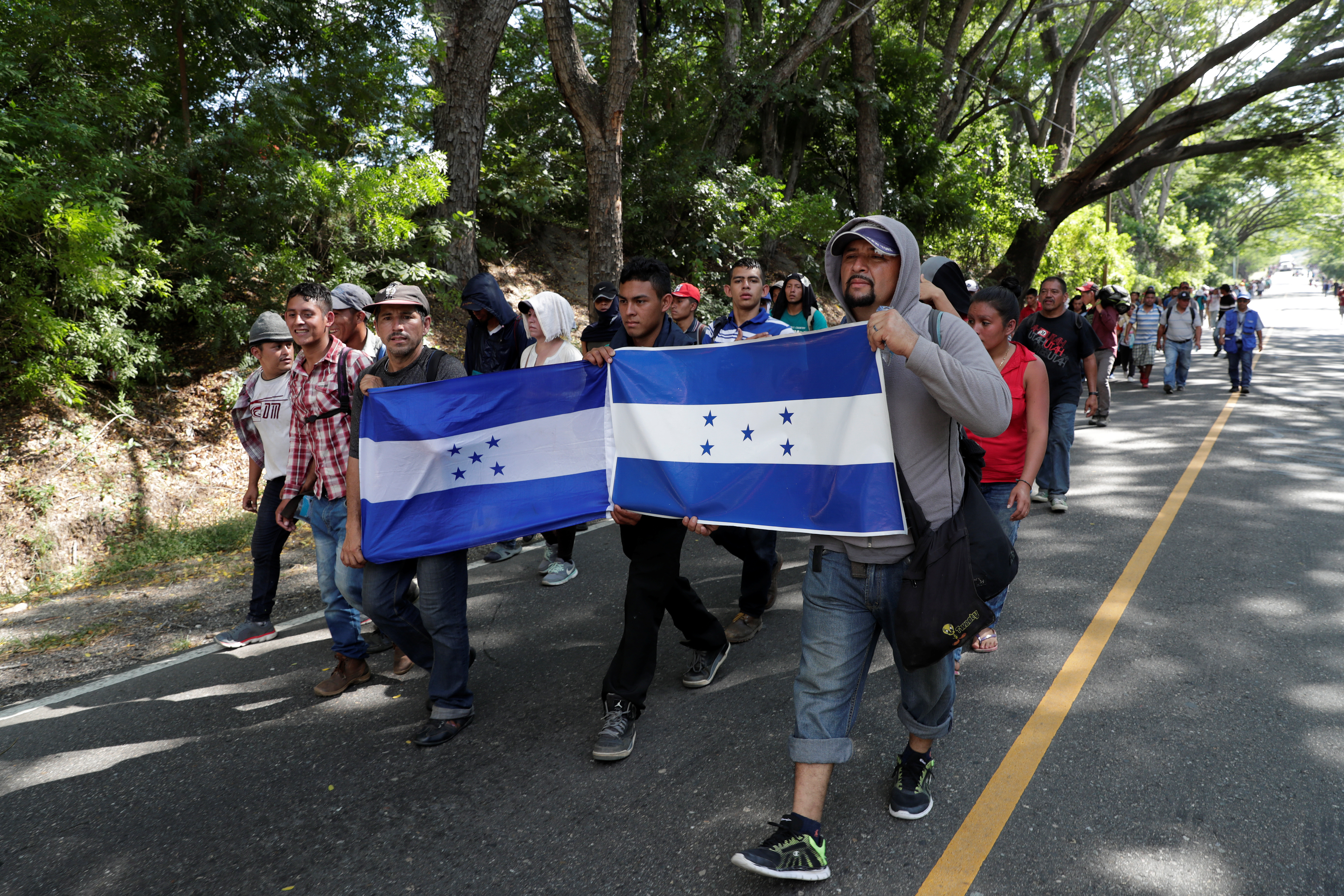 Honduran migrants, part of a second wave of migrants heading to the U.S., hold Honduran flags as they continue their journey to the Mexican border with other Central American migrants, in Chiquimula, Guatemala October 23, 2018. REUTERS/Luis Echeverria