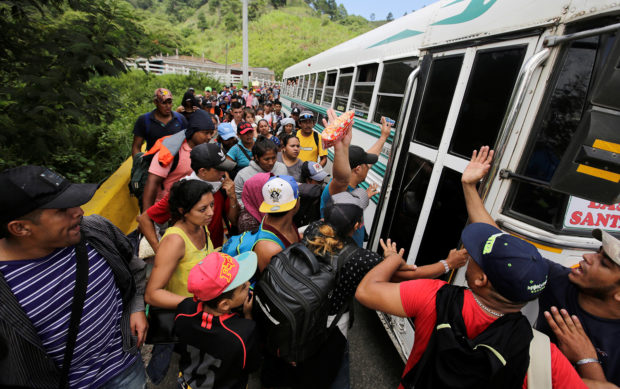 Hondurans fleeing poverty and violence hitchhike as they move in a caravan toward the United States, in the west side of Honduras October 14, 2018. REUTERS/ Jorge Cabrera