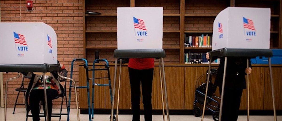 Iva Woke (L), a 100-year-old resident living in Chestertown, Maryland, casts he ballot in a voting booth as others do the same at the Kent County Public Library in Maryland's early voting on October 25, 2018. (Photo by Jim WATSON / AFP) (JIM WATSON/AFP/Getty Images)