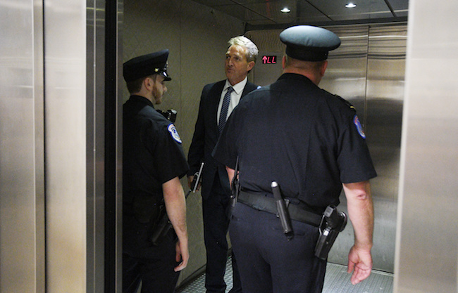 Senator Jeff Flake (R-AZ) boards a U.S. Senate elevator with Capitol police officers after reading the FBI's report on their investigation into sexual assault allegations against U.S. Supreme Court nominee Judge Brett Kavanaugh on Capitol Hill in Washington, October 4, 2018. REUTERS/Yuri Gripas