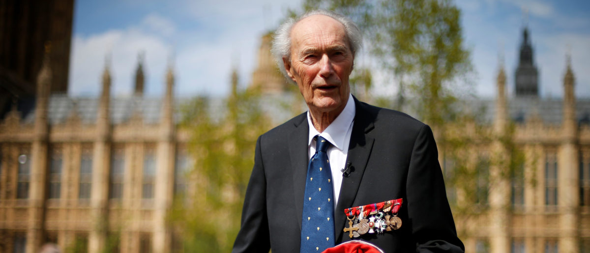 FILE PHOTO: World War Two Norwegian resistance fighter Joachim Roenneberg holds up a Union flag, which had been lowered from above the House of Lords, after it was presented to him by the Clerk of the House of Lords in Westminster, London, April 25, 2013. REUTERS/Andrew Winning