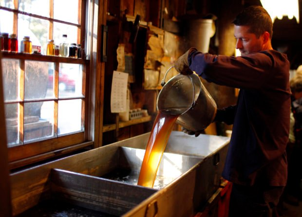 Steve Randle, a software engineer during the work-week, pours freshly made maple syrup in the finishing pan at Hollis Hills Farm in Lunenburg
