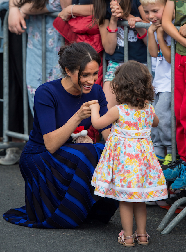 Meghan, Duchess of Sussex, holds hands with a young girl during a walkabout in Rotorua on day four of the royal couple's tour of New Zealand October 31, 2018. Dominic Lipinski/Pool via REUTERS