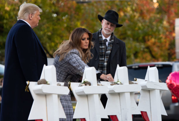US President Donald Trump and First Lady Melania Trump, alongside Rabbi Jeffrey Myers, place stones and flowers on a memorial as they pay their respects at the Tree of Life Synagogue in Pittsburgh, Pennsylvania, October 30, 2018. (SAUL LOEB/AFP/Getty Images)