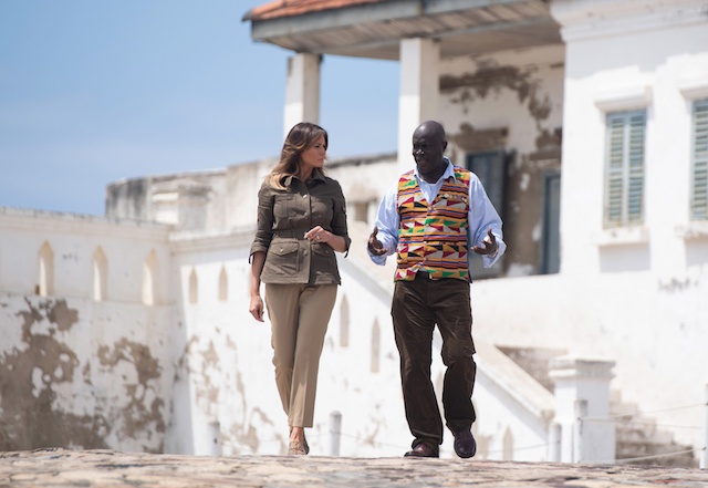 US First Lady Melania Trump (L) tours with Museum Educator Kwesi Essel-Blankson, the Cape Coast Castle, a former slave trading fort, in Cape Coast, Ghana, on October 3, 2018. - US First Lady Melania Trump is on a solo tour of Africa to promote her children's welfare programme. (Photo credit: SAUL LOEB/AFP/Getty Images)