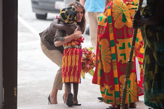 US First Lady Melania Trump hugs a young girl as she arrives at the Emintsimadze Palace in Cape Coast, Ghana, on October 3, 2018. - US First Lady Melania Trump is on a solo tour of Africa to promote her children's welfare programme. (Photo credit: SAUL LOEB/AFP/Getty Images)