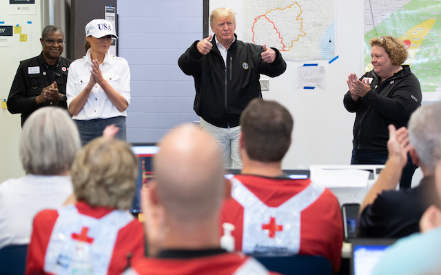 US President Donald Trump and First Lady Melania Trump meet with Red Cross workers in Macon, Georgia, October 15, 2018. - President Donald Trump toured areas of Florida devastated by Hurricane Michael last week, and met some of the thousands of people still struggling to survive without running water or electricity. Trump's tour took him past the base before he took off again in Air Force One for Georgia, which also suffered damage as the storm plowed across the southeast of the country. (Photo credit: SAUL LOEB/AFP/Getty Images)